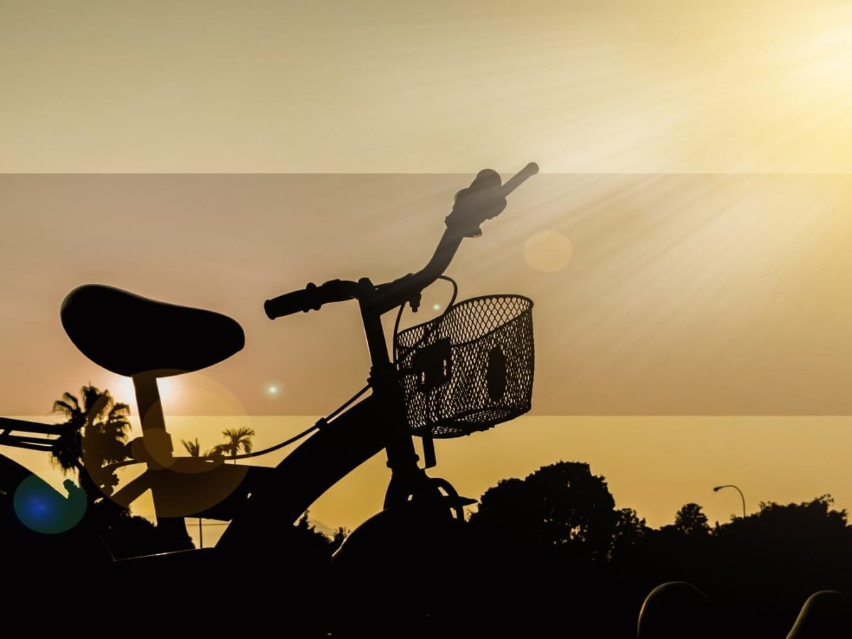 Silhouette view of adult tricycle at sunset with small front basket