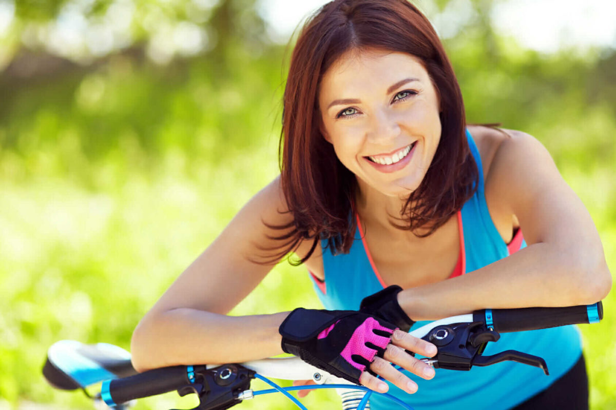 Smiling woman leaning on an adult tricycle wearing pink cycling gloves and workout clothes